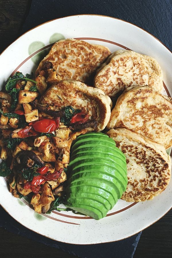 savoury vegan pancakes tofu scramble and avocado breakfast on a plate