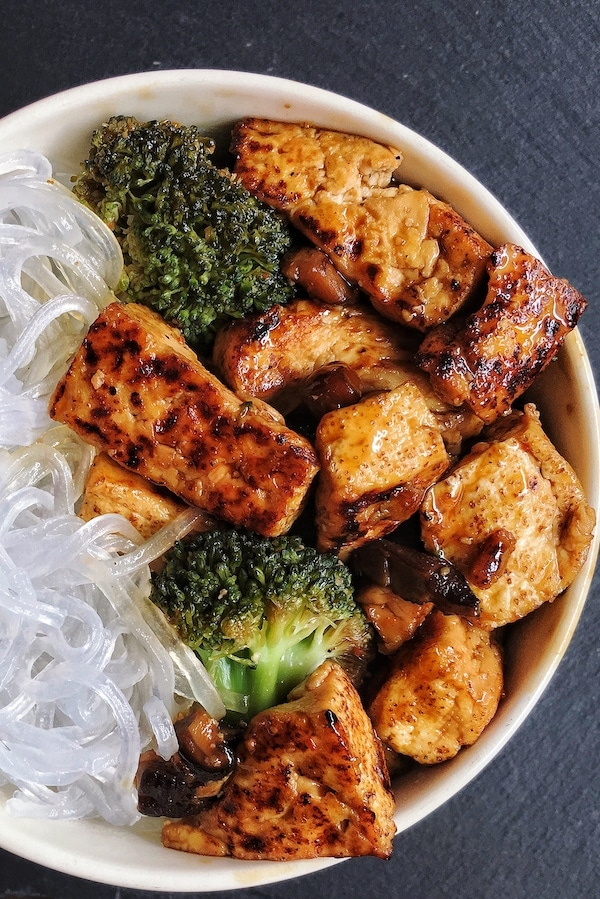 vegan teriyaki tofu stir fry with broccoli and japanese noodles in a bowl