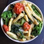 vegan casarecce pasta with spinach tomatoes and broccoli in a bowl