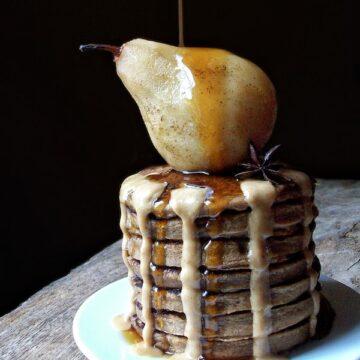 stack of vegan pancakes with poached pears drizzled with maple syrup and hazelnut butter on a plate