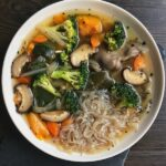 vegan vegetable soup with konjac noodles in a white bowl
