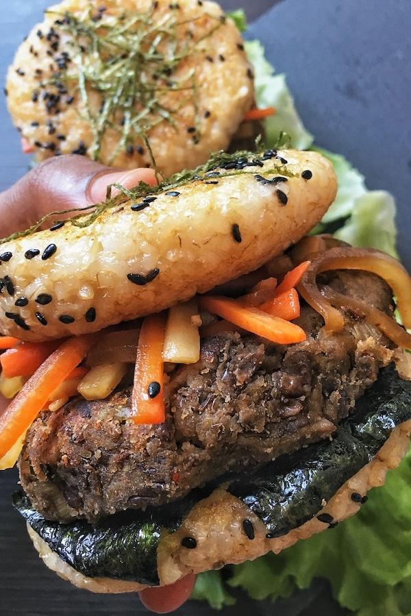hand holding rice bun burger with kimpira
