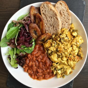 tofu scramble baked beans plantains toast and salad greens in a plate