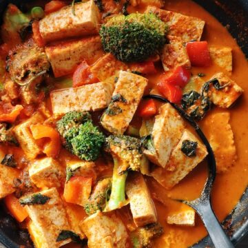 vegan thai red curry with tofu in a pan with spoon
