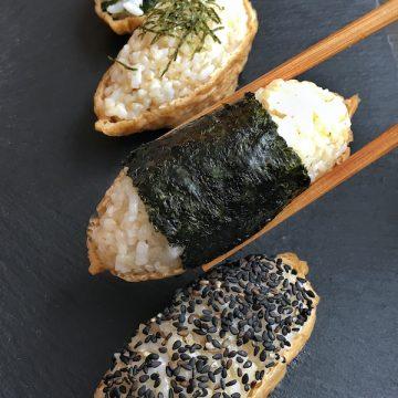 vegan inari sushi on slate plate with chopsticks
