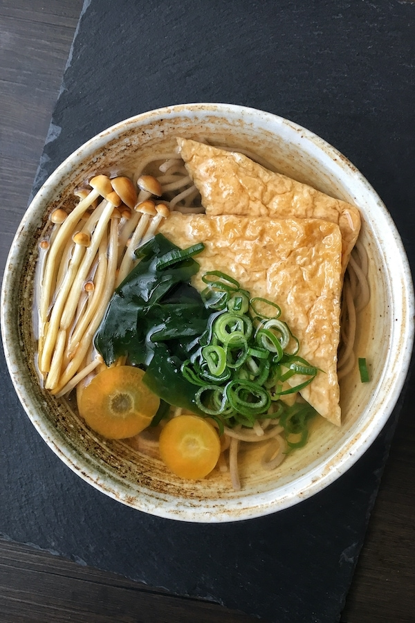 vegan kitsune soba with aburaage and toppings in a bowl