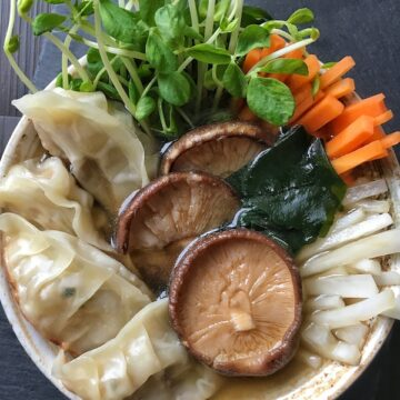 vegan gyozas with asian vegetables and soup in a bowl